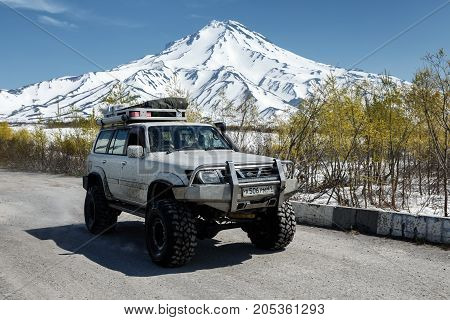 KAMCHATKA PENINSULA RUSSIAN FAR EAST - JUNE 18 2017: Four-wheel drive japanese car - SUV Nissan Safari rides on country mountain road against background of snow-capped cone of Vilyuchinsky Volcano