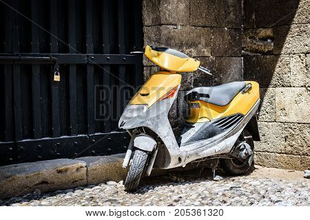 RHODES, GREECE - AUGUST 2017: Scooter at narrow street of Rhodes town on Rhodes island, Greece