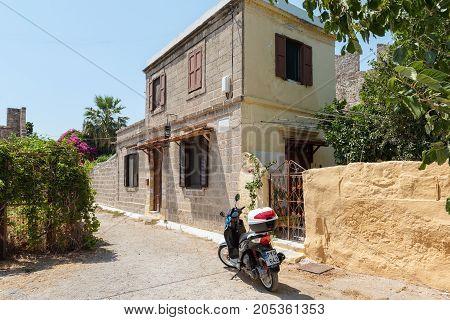 RHODES, GREECE - AUGUST 2017: Motorbike parked near traditional Greek house in Rhodes town on Rhodes island, Greece