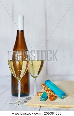 Bottle and two glasses of white wine and variation of ucommon cheeses on a wooden background