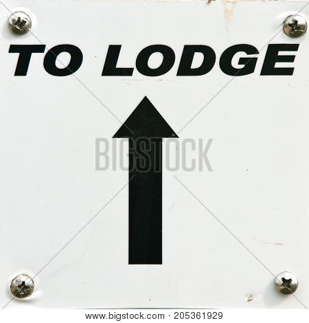 To lodge black direction arrow sign on white