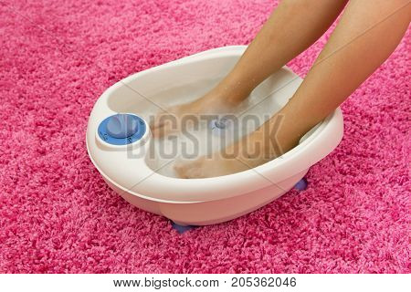Female feet in a vibrating foot massager home on a pink background. Electric massage foot bath included