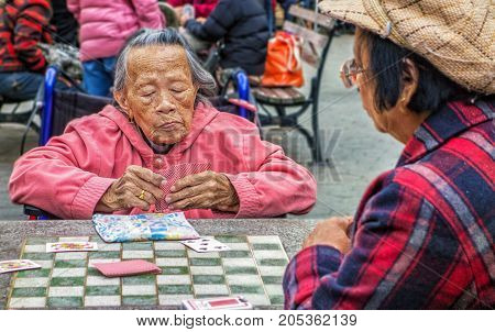 Women Play Cards In New York City Chinatown Park