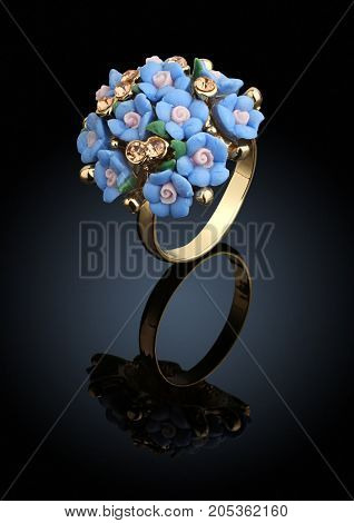 Jewelry ring in shape of flower on black with reflection