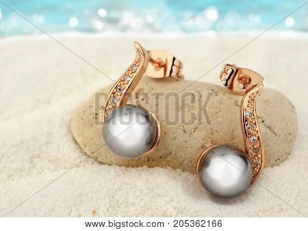 Jewelry earrings with black pearls on sand beach background copy space