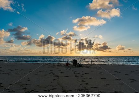 beach chair and fishing pole on the beach on an early summer morning