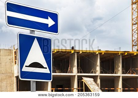 blue road sign pointer on construction of frame building in the city