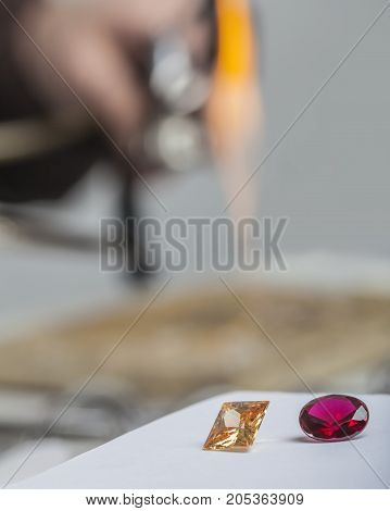 Close up image of two precious stones situated on a desk in the jeweler's workshop.