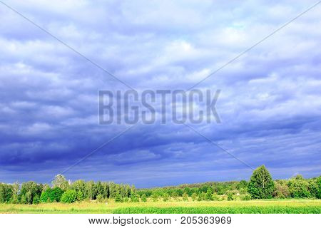landscape with dark thundercloud clouds under the forest and land