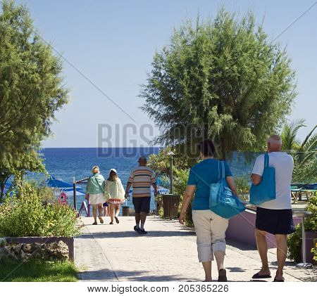 people walking to the beach - beach holiday