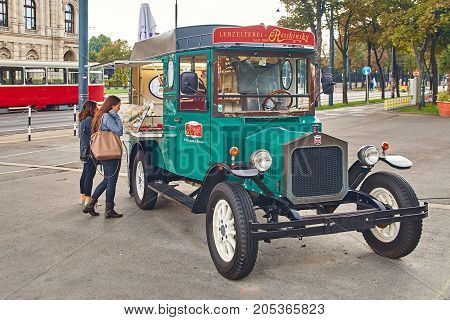 Vienna, Austria - September 22, 2014: Tourists near movable gingerbread and candy shop in the form of an old car on the street.