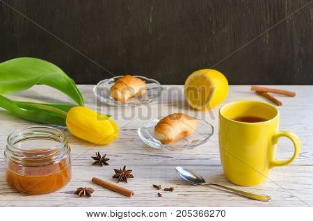 Breakfast of tea croissant and honey on white wooden background.