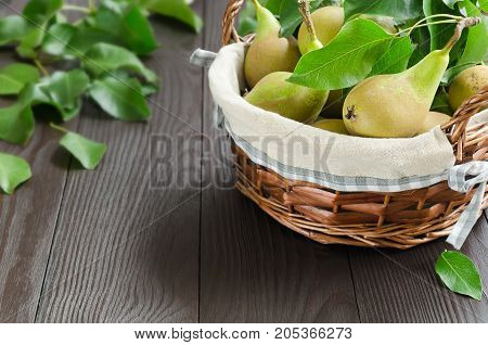 Basket with pears on dark wooden background. Harvest concept. Selective focus