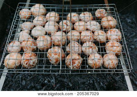 fried champignon mushrooms on charcoal grills closeup