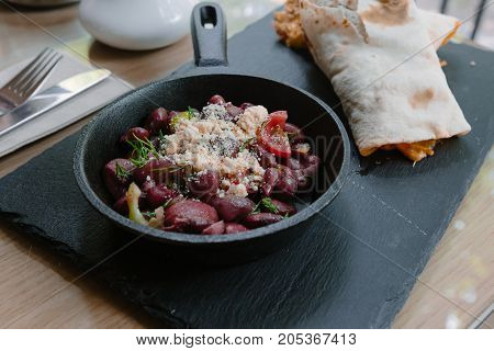 Fried beans in a frying pan in a restaurant