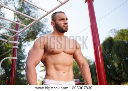 Healthy handsome and active man with fit muscular body, after doing exercises. Sporty athletic male training outdoor.