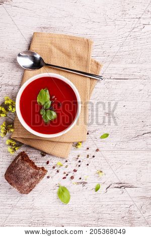 Soup in a bowl with dill, sour cream and black bread on wooden background. National dish of Ukrainian cuisine.