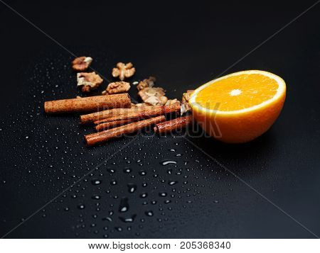 A composition of walnuts, juicy oranges and cinnamon on a black background. Copy space.