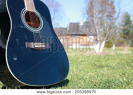 guitar acoustic black glossy six-string playing in nature