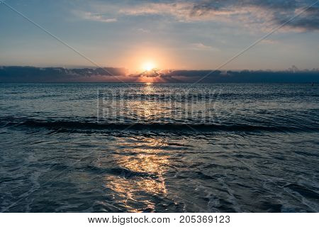 bright sunlight and blue sky reflecting off the ocean on a calm morning at the beach