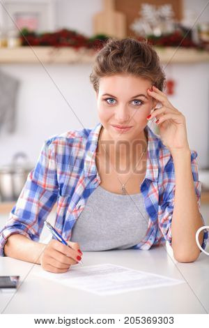 Happy beautiful woman standing in her kitchen writing on a notebook at home.