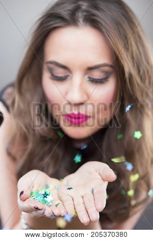 Happy Caucasian Brunette Woman Holding New Year Confetti in Hands And Blowing Them Around. Against Gray Background.Focus on hands.Vertical Image