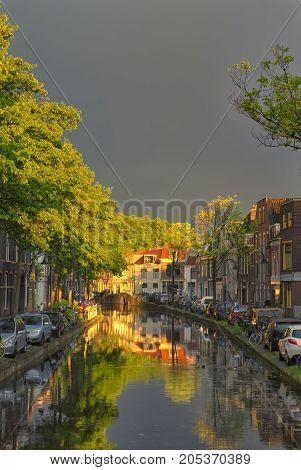 Travel Concepts and Ideas. Traditional Dutch Channels Located in Old City Delft. Picture Taken During amazing Picturesque Sunlight Straight After the Rain with Grey Clouds.Vertical Image