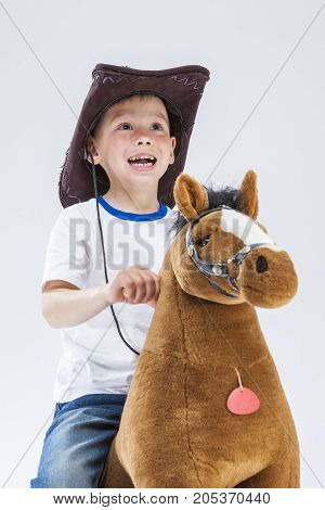 Happy Smiling and Glad Caucasian Little Boy in Cowboy Clothing Riding a Symbolic Plush Horse. Standing Against White Background. Looking Upwards. Vertical Composition