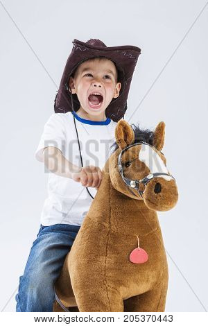 Portrait of Shouting Caucasian Little Boy in Cowboy Clothing Riding a Symbolic Plush Horse. Standing Against White Background. Looking Upwards. Vertical Composition