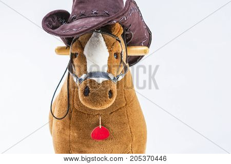Children's Brown Plush Toy Horse With Natural Cowboy Stetson. Placed Against White Background. Horizontal Image