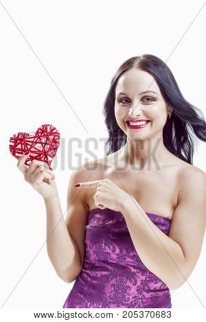 Portrait of Happy Smiling Positive Caucasian Woman with Red Wicker Heart. Poirnting With Finger. Against White. Vertical Image