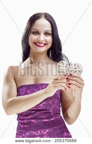 Portrait of Happy Smiling Caucasian Woman with White Wicker Heart Holding. In Front of Herself. Vertical Shot
