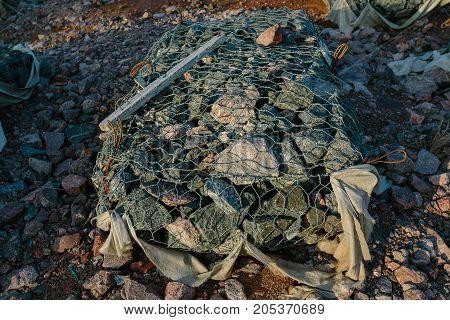 Granite stones in a metal grid close-up