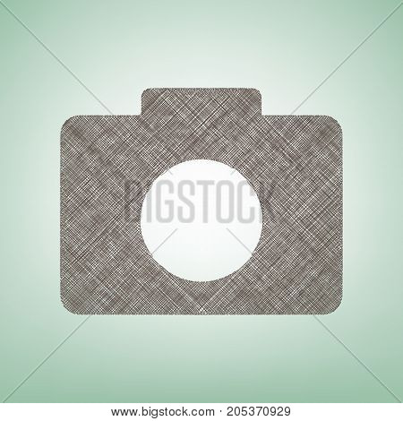 Digital camera sign. Vector. Brown flax icon on green background with light spot at the center.