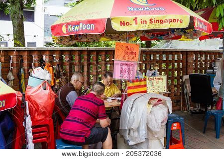 SINGAPORE - SEPTEMBER 7 2017: A fortune teller practices divination for devotees outside the Kwan Im Thong Hood Cho Temple on Waterloo Street in Bugis. The area is a famous haven for fortune tellers.