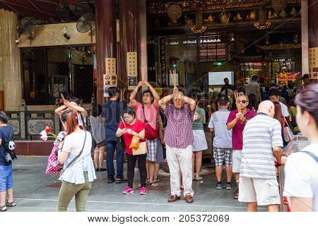 SINGAPORE - SEPTEMBER 7 2017: Worshippers flock to the historical Kwan Im Thong Hood Cho Temple to pray during the Hungry Ghost Festival. Since 1884 this Chinese Goddess of Mercy temple has attracted devotees to worship from around the world.