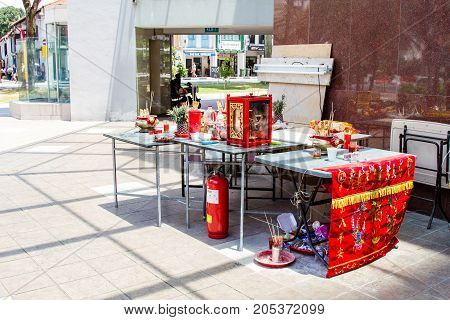SINGAPORE - SEPTEMBER 7 2017: A makeshift Chinese altar was erected at a street corner to make offerings to spirits during the Hungry Ghost Festival on the seventh month on the lunar calendar. ohttps://static1.bigstockphoto.com/5/0/2/small2/205372099.jpg