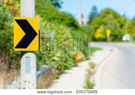 Black on yellow chevron road sign attached to post indicating right turn against blurry curving road in background.