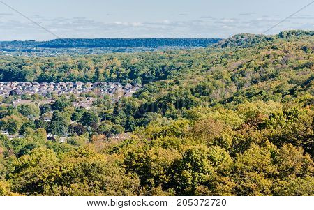Escarpment and hills with suburbs encroaching on dense forest receding into distance in early autumn leaf colors in southern Ontario Canada.