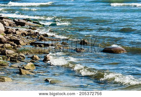 Rocky shore with small incoming waves breaking and churning on wet stones.