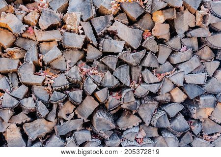 Pile of dry gray stacked firewood with some autumn leaves.