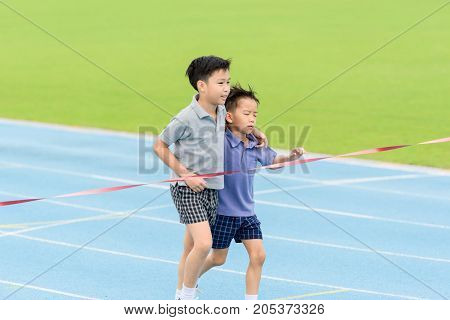 Young Asian Boy Running On Blue Track In The Stadium
