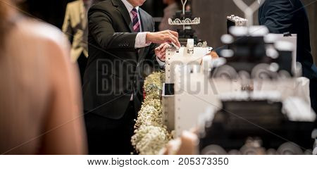 Business man puts envelope or greeting card for bridegroom in white box into wedding box on wedding reception table.