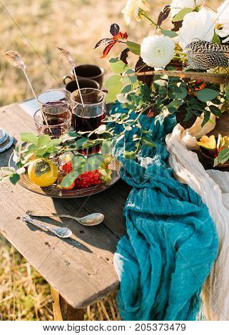 cutlery, picnic, romance concept. on the table in park there are few cups and glasses with tea, silver plate with rowan berries and orange persimmon, some ancient silverware