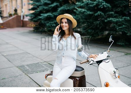 Beautiful Young Woman Dressed Casual Sitting On Scooter And Talking On Phone. Girl Sitting On The Bi