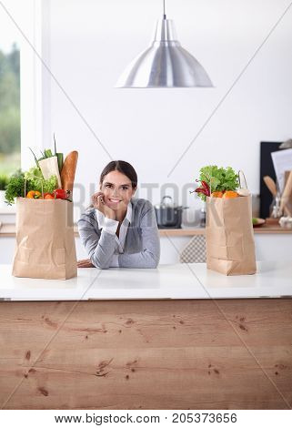 Young woman holding grocery shopping bag with vegetables .Standing in the kitchen.