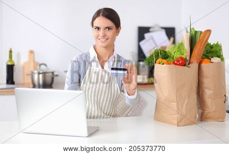 Smiling woman online shopping using computer and credit card in kitchen.