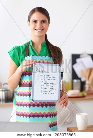 Woman in the kitchen at home, standing near desk with folder.