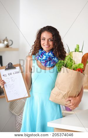 Young woman holding grocery shopping bag with vegetables . Standing in the kitchen.