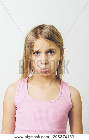 a little girl pouting in front of camera.
